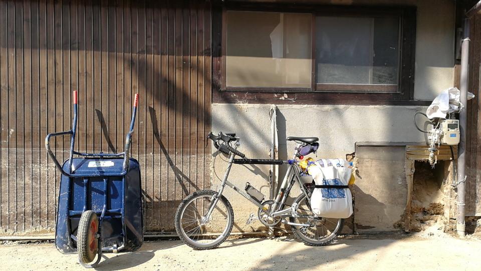 坂町小屋浦2丁目にて(自転車の下には土砂がまだ数10cm堆積している)